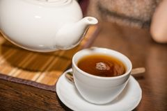 Pour tea from a teapot into a mug Stock Images