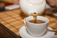 Pour tea from a teapot into a mug Royalty Free Stock Photography