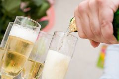 Pour champagne. Pouring champagne in two glasses Stock Image