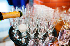 Pour champagne into glasses at wedding party.  Stock Photos