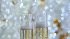 Pour the champagne in the wine glasses. Garland in the background in the bokeh.  stock video