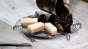 Pour the chocolate mirror glaze on a delicious mousse dessert. Liquid tasty sweet dessert cooking. Pour the chocolate mirror glaze on a delicious mousse dessert stock video footage