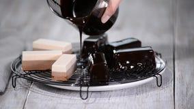 Pour the chocolate mirror glaze on a delicious mousse dessert. Liquid tasty sweet dessert cooking. Pour the chocolate mirror glaze on a delicious mousse dessert stock video