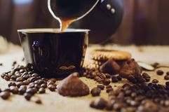 Pour the coffee into the cup. Coffee beans and sweets background stock photos