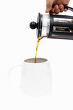 Pour coffee. A hand pouring coffee from a french-press coffee maker Stock Image