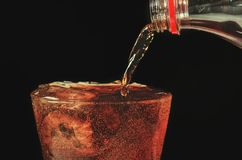 Pour cola from the bottle to glass and bubble soda on black back. Ground Royalty Free Stock Photo