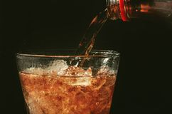 Pour cola from the bottle to glass and bubble soda on black. Background Royalty Free Stock Images