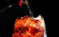 Pour cola in a glass with ice on black background. Pour cola in a glass with ice on black background Stock Photo
