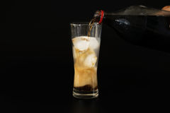 Pour the cola from a plastic bottle into a glass of ice Royalty Free Stock Photos