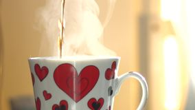 Pour a cup of hot drink. Slow motion. Closeup. stock video footage
