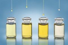 Pour des bouteilles avec différents cosmétiques huilez les supports sur le fond métallique de texture de gradient bleu Photo libre de droits