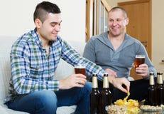 Pour deux hommes avec de la bière reposez-vous et parlez Photo libre de droits