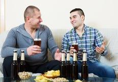 Pour deux hommes avec de la bière reposez-vous et parlez Image libre de droits
