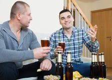 Pour deux hommes avec de la bière reposez-vous et parlez Image stock