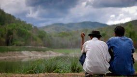 Pour deux hommes parlez du lac et de la forêt Photos stock