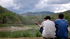 Pour deux hommes parlez du lac et de la forêt Photo stock