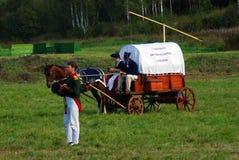 Pour deux personnes reposez-vous dans un chariot en bois Un soldat-reenactor se tient prêt le Photo libre de droits