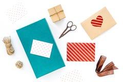Pour envelopper le cadeau Boîte, papier, enveloppe, corde mince, carte de voeux, ruban, sciccors sur le copyspace blanc de vue su images stock