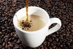 Pour espresso. Espresso coffee pouring into ceramic cup Stock Photo