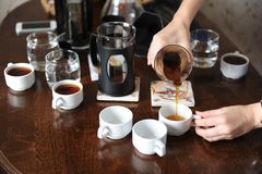 Pour freshly brewed coffee from a glass jug on white cups Stock Photos