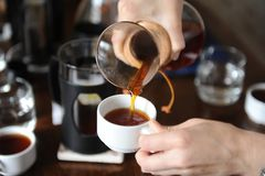 Pour freshly brewed coffee from a glass jug on white cups close up Royalty Free Stock Images