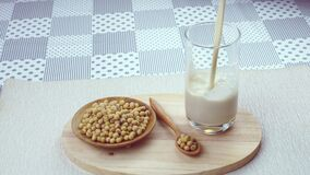 Pour freshly prepare homemade soy milk or soybeans milk into a glass on a wooden board.