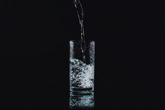 Pour into a glass. Show motion of water pour into a glass Royalty Free Stock Photography