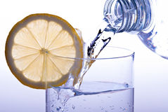 Pour glass of water with lemon. Water is poured into a glass of lemon Stock Photography