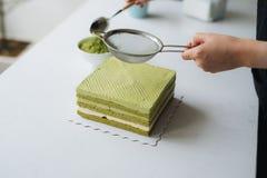 Pour green tea powder over delicious cheesecake Stock Image