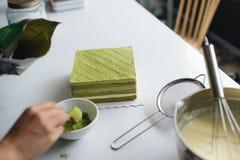 Pour green tea powder over delicious cheesecake Stock Photos
