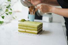 Pour green tea powder over delicious cheesecake Royalty Free Stock Images