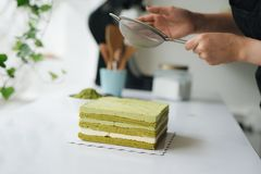 Pour green tea powder over delicious cheesecake Royalty Free Stock Image