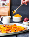 Pour honey roasted pumpkin slices with cinnamon on parchment Stock Photos