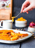 Pour honey roasted pumpkin slices with cinnamon on parchment Royalty Free Stock Photography