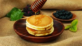 Pour honey by a wooden dipper stick on a pile of pancake in a wooden bowl