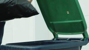 Pour jeter un sac des déchets dans la poubelle, plan rapproché clips vidéos