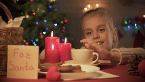 Pour la note de Santa sur la table, tasse de biscuits de cacao et de gingembre, fille souriant à la caméra clips vidéos