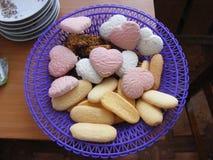 Pour la pause café de Saint-Valentin : coeur-biscuits de rose et blancs mignons avec d'autres bonbons du plat violet sur la table image libre de droits