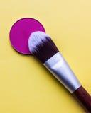 Pour le maquillage Nuance lumineuse avec la brosse sur un fond jaune image libre de droits