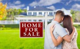 Pour le signe de Real Estate de vente, couples militaires regardant la Chambre Photographie stock