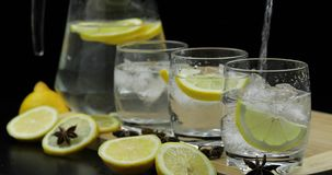 Pour lemon juice into glass with ice and lemon slices. Lemon alcoholic cocktail royalty free stock photography