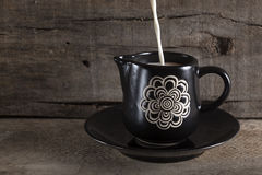 Pour milk into a black cup Royalty Free Stock Photo