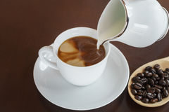 Pour milk into a cup of fresh coffee Royalty Free Stock Images