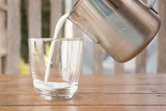 Pour milk from a pitcher into a glass Royalty Free Stock Photography