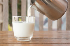 Pour milk from a pitcher into a glass Royalty Free Stock Photos