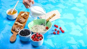 Pour milk in porridge. Healthy and tasty breakfast with crispybread, berries, honey and nuts. Flat lay. copy space. Authentic life royalty free stock photo