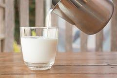 Pour mjölkar från en kanna in i ett exponeringsglas Royaltyfria Foton