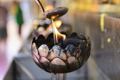 Pour oil with a burning in stainless steel lamp.  Royalty Free Stock Photography