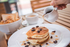 Pour pure honey into pancake Royalty Free Stock Image