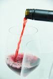 Pour the red wine in the glass. Pour the red wine in the transperend glass on the white background Stock Photos